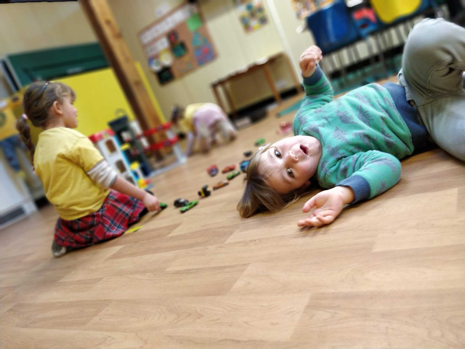 A boy playing on the floor whilst girls play behind him at Rottingdean Whiteway Nursery