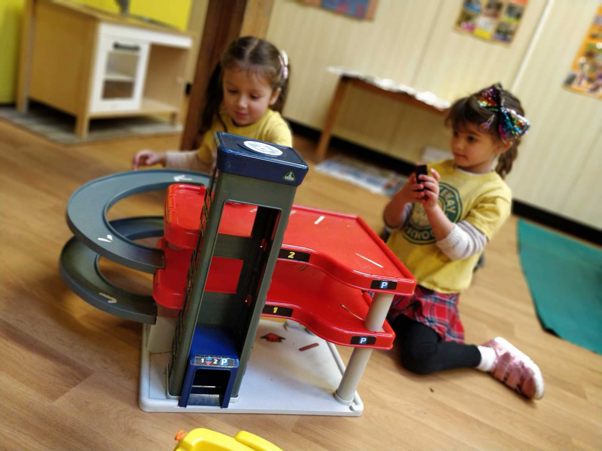 Two girls playing with a car garage at Whiteway PreSchool