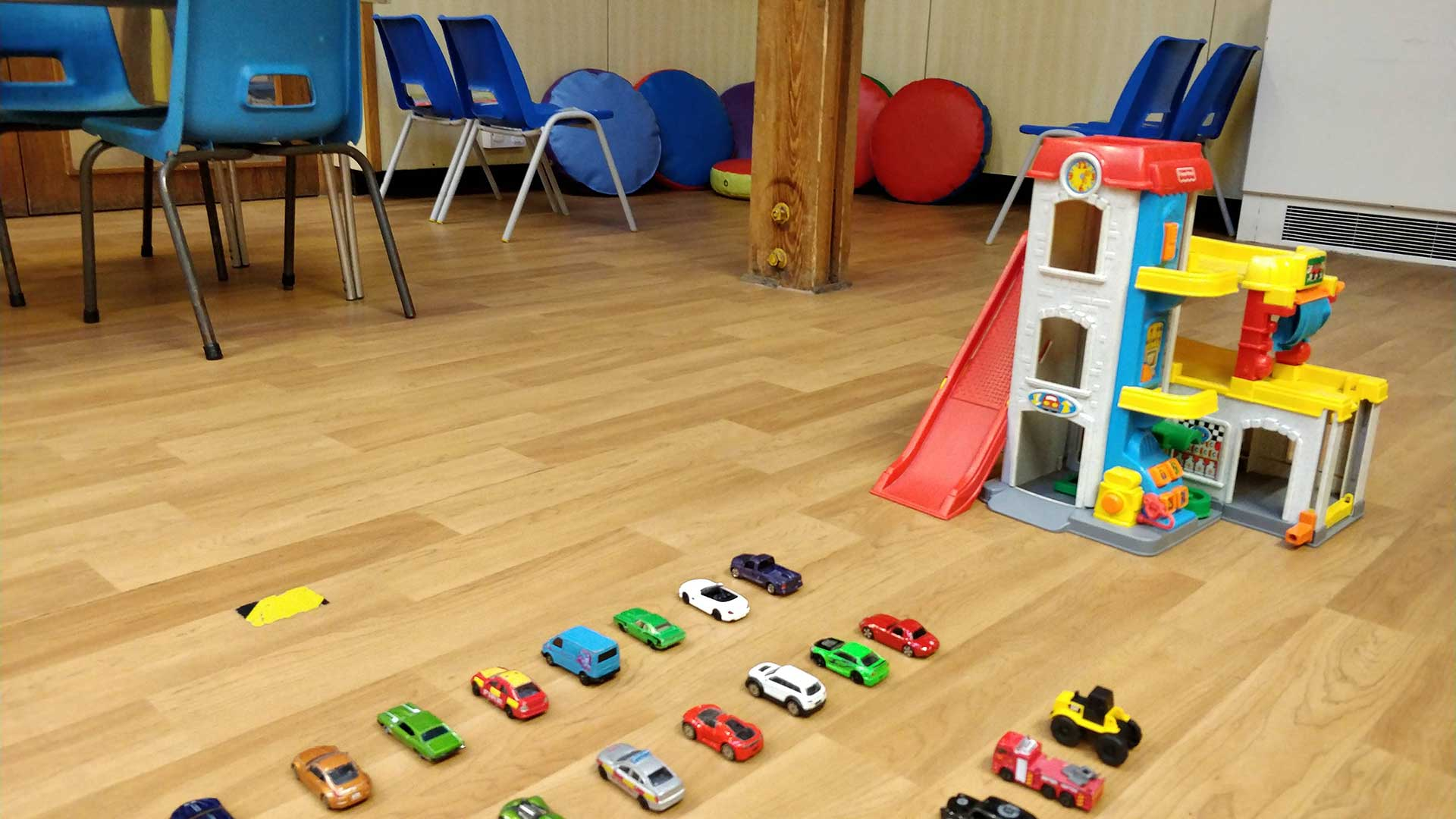 Cars and a play garage laid out on the floor at Rottingdean Whiteway Pre-School