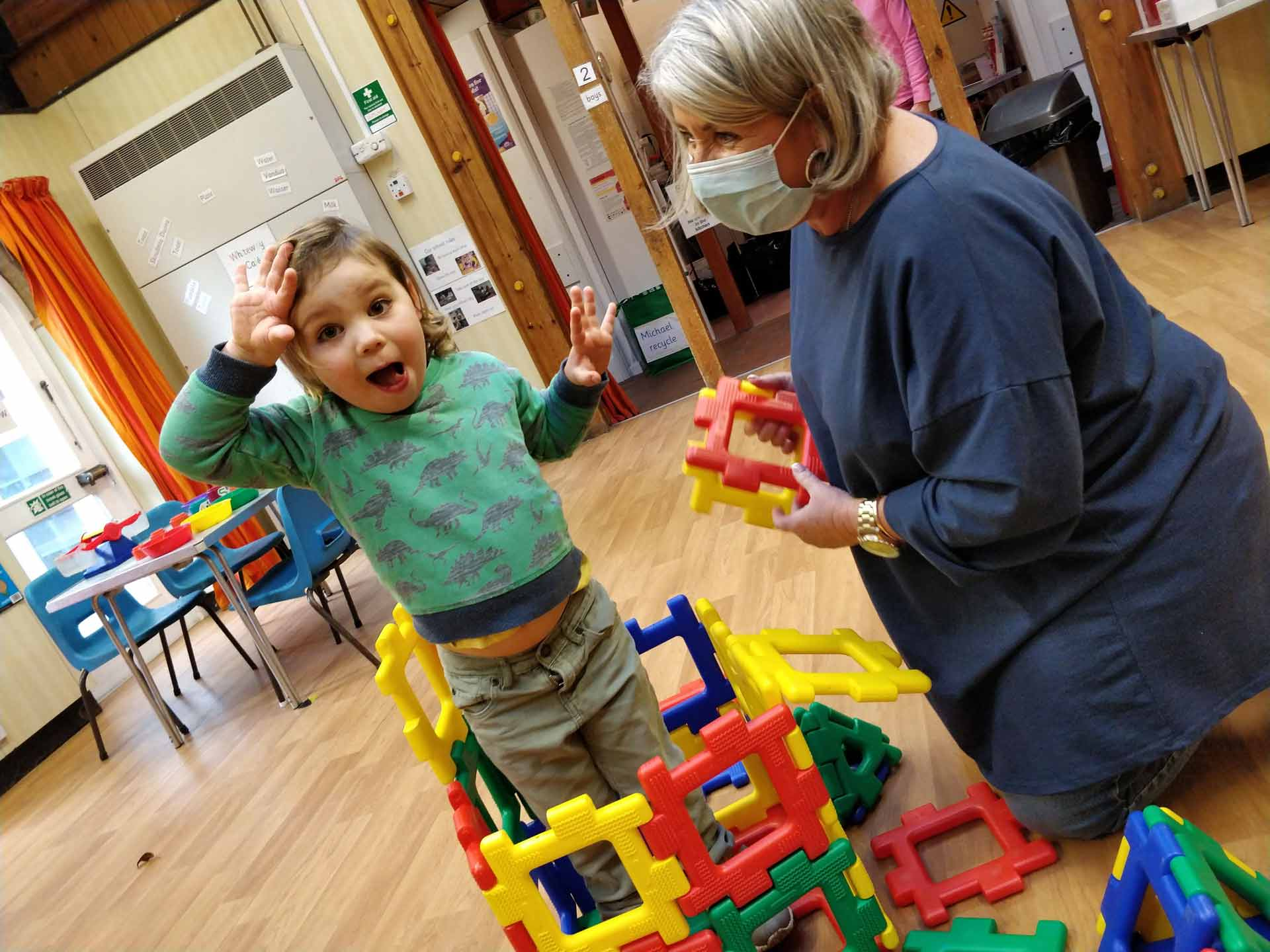 Boy playing in Whiteways in building blocks with child carer