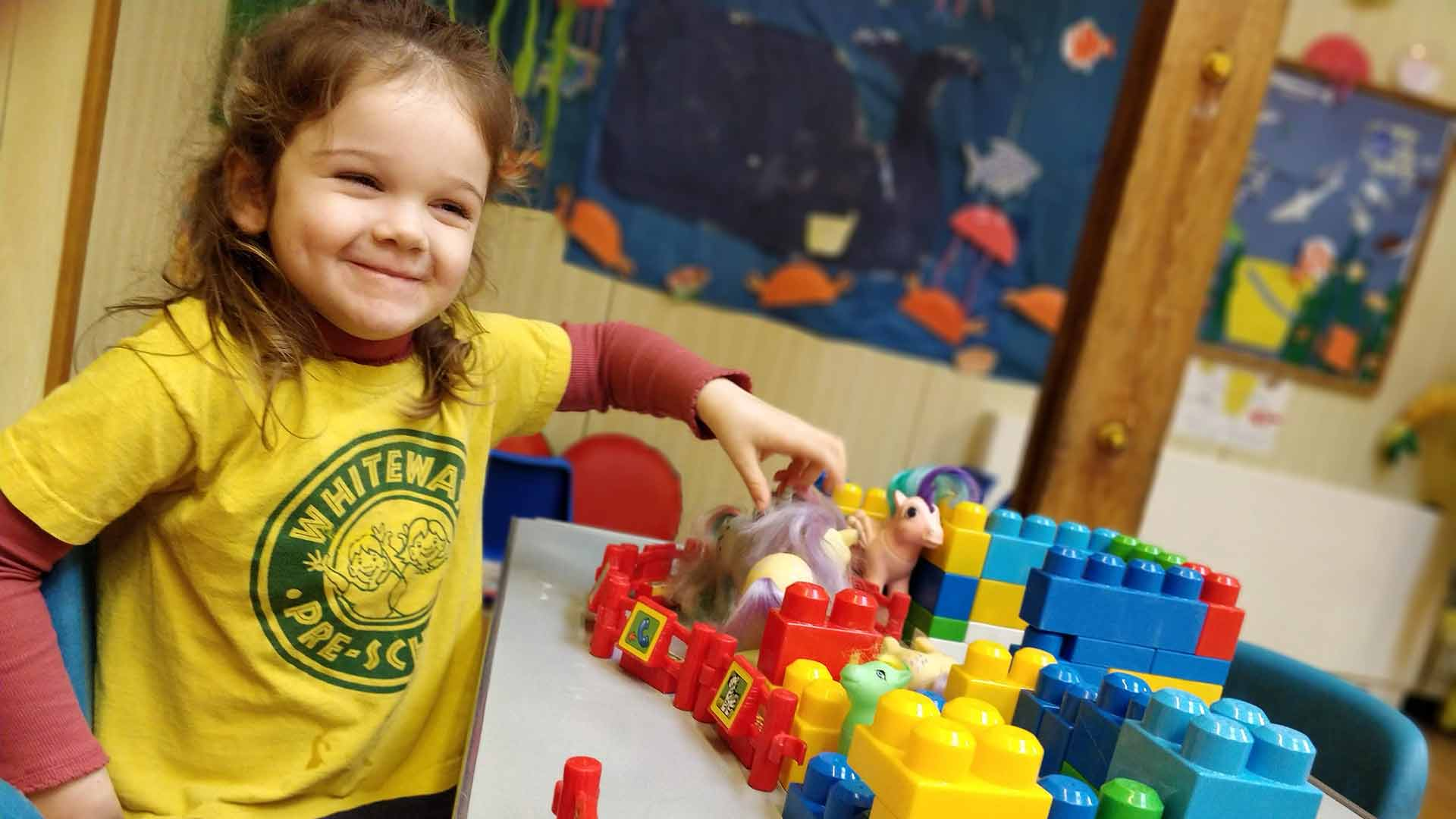 A young girl looking happy playing with a pony toy at Rottingdean Whiteway Pre-School