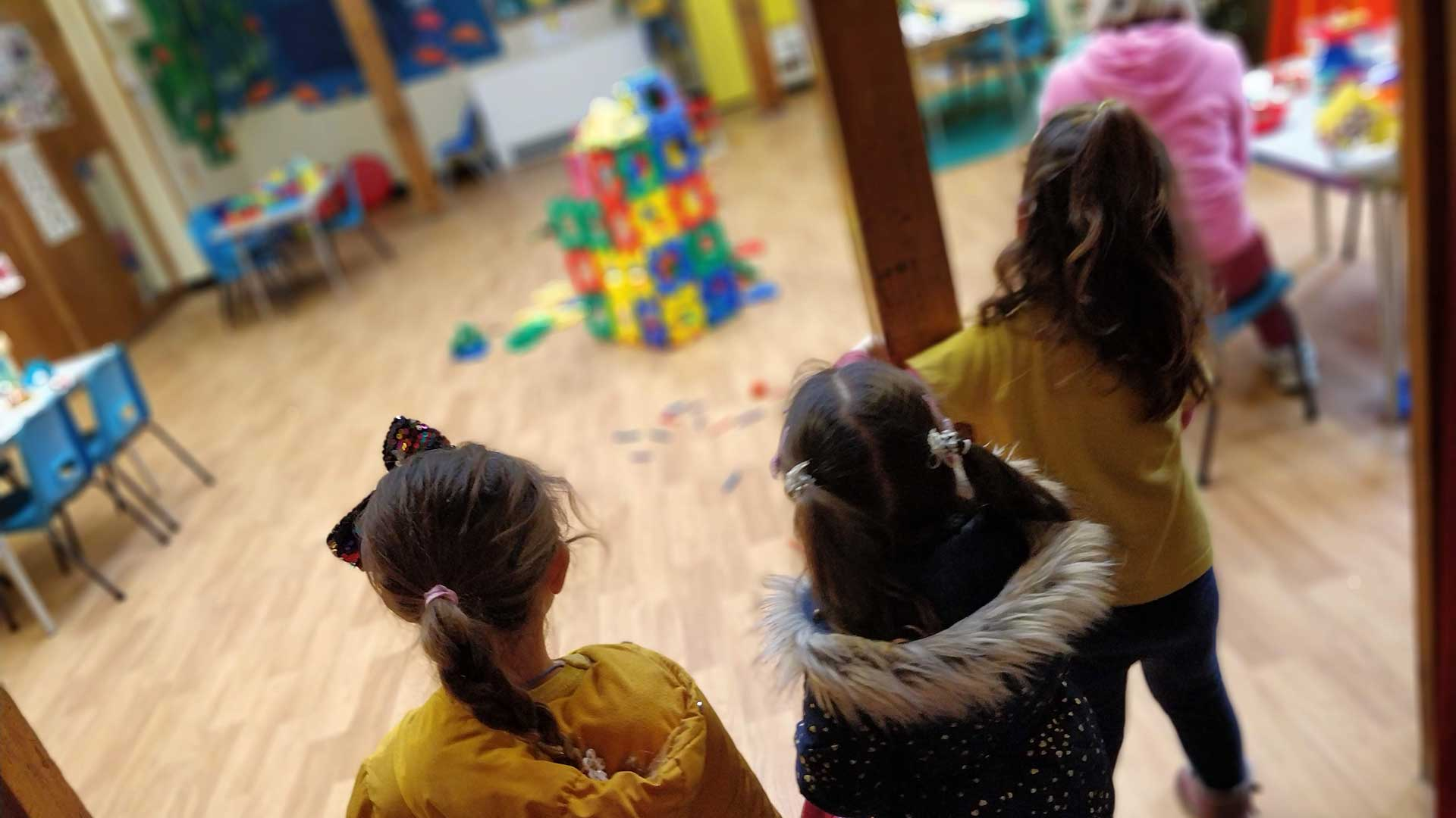 Girls arriving at Rottingdean Whiteway Pre-School. looking into the hall