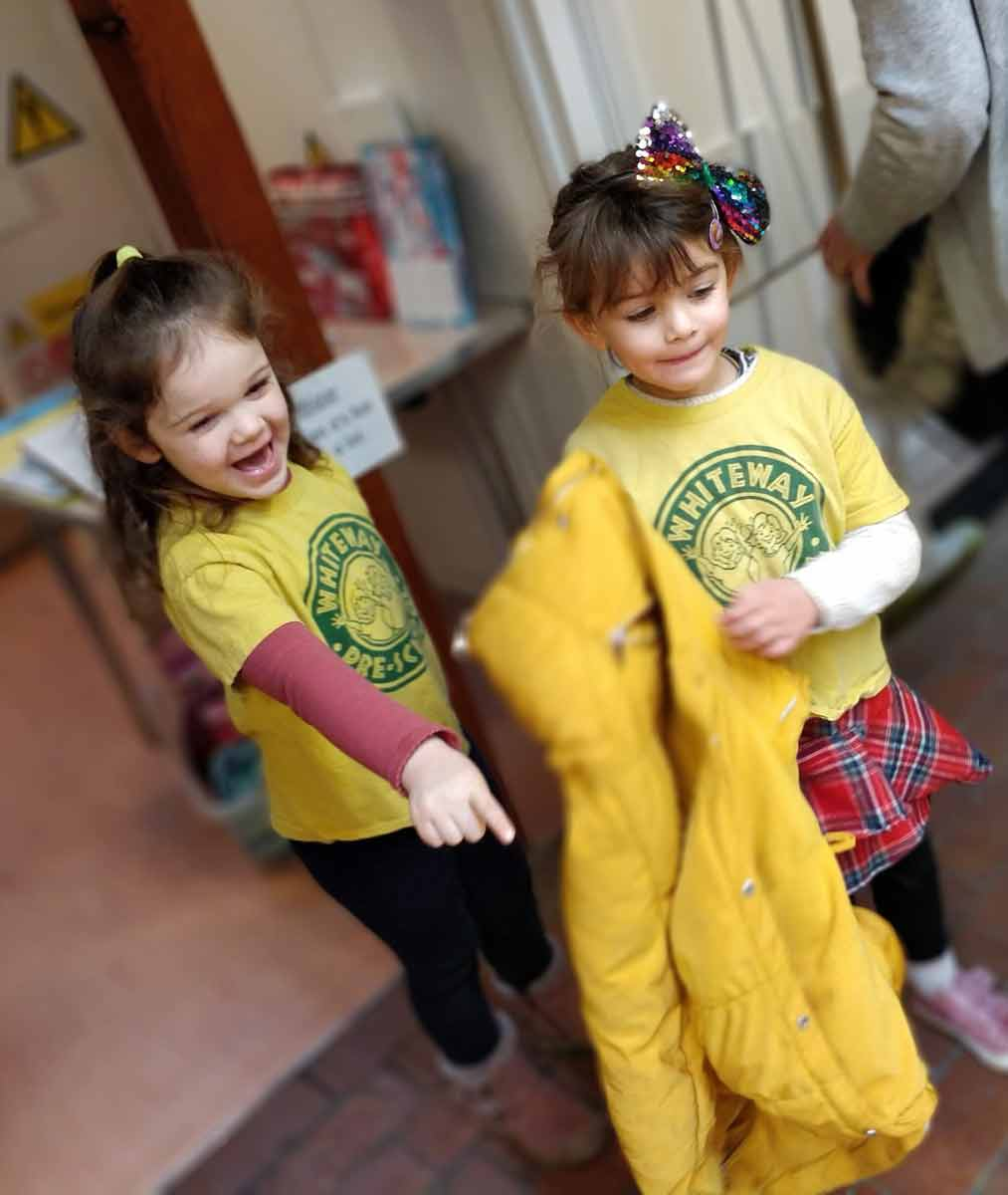 Two girls excitedly looking into the hall at Rottingdean Whiteway Pre-School