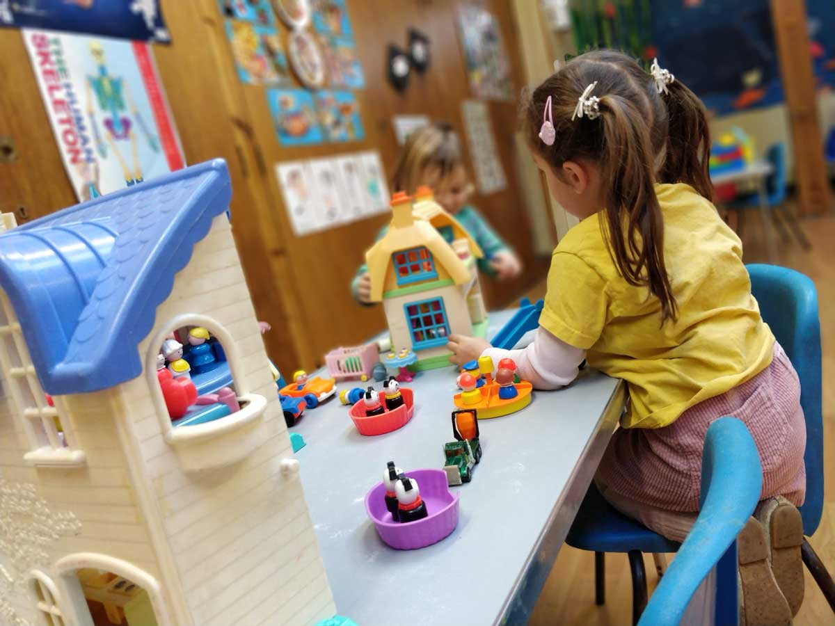 A girl playing at a table in Rottingdean Whiteway Pre-School