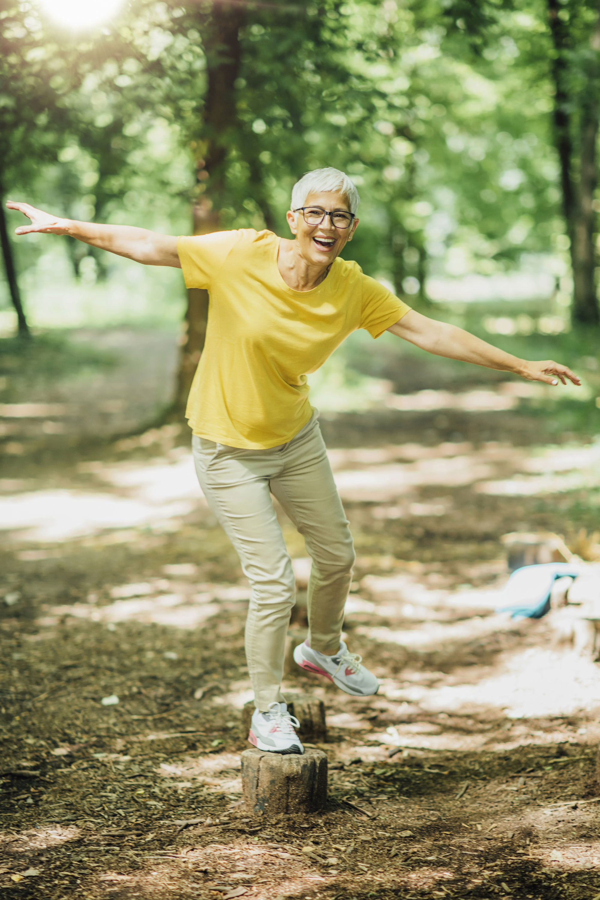 Mid aged lady balancing on tree stomps in a forest. Wearing a yellow shirt and beige pants.