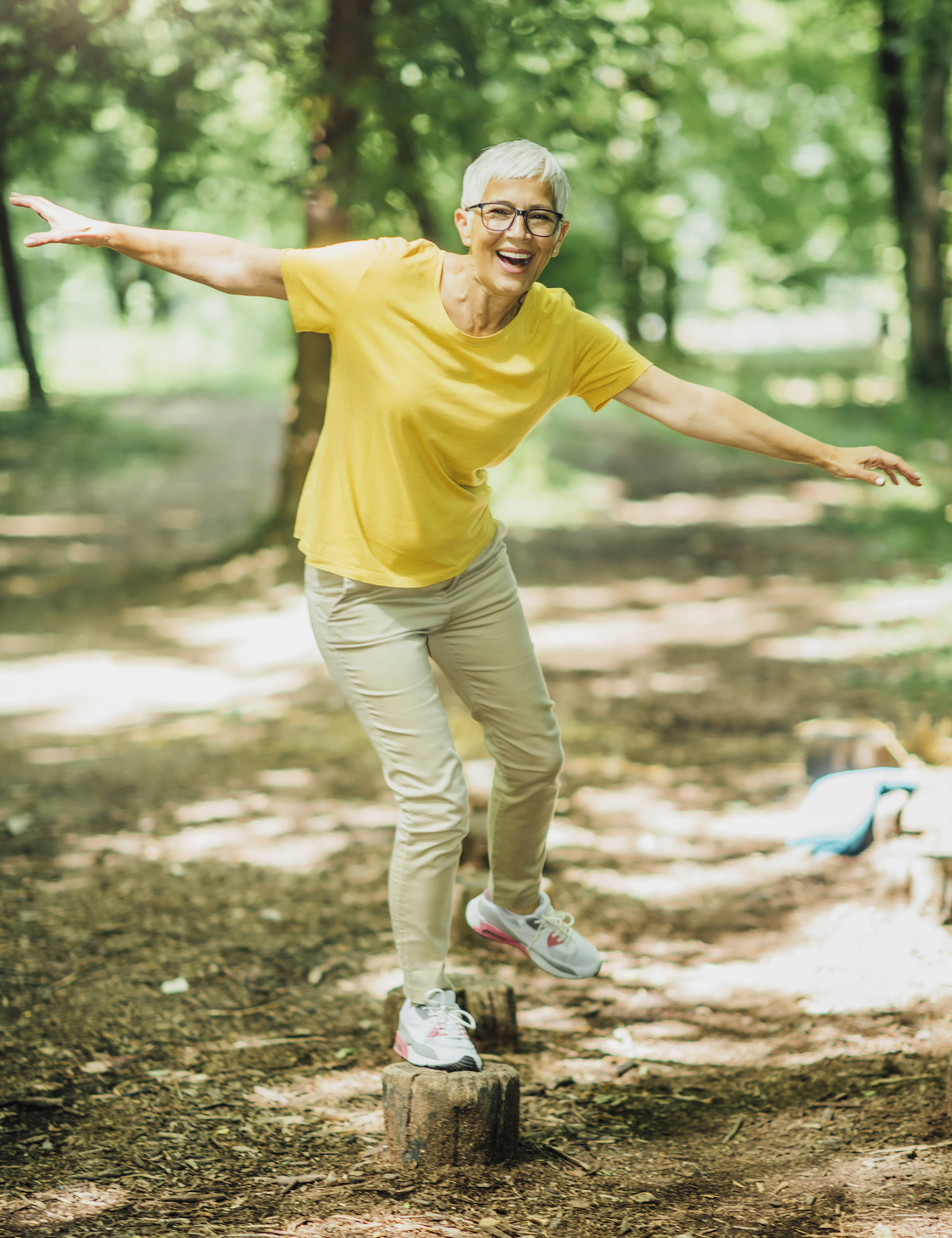 Happy and fit mid-aged woman balancing on a tree stomp in a sunny forest. Wearing a yellow shirt and beige pants.