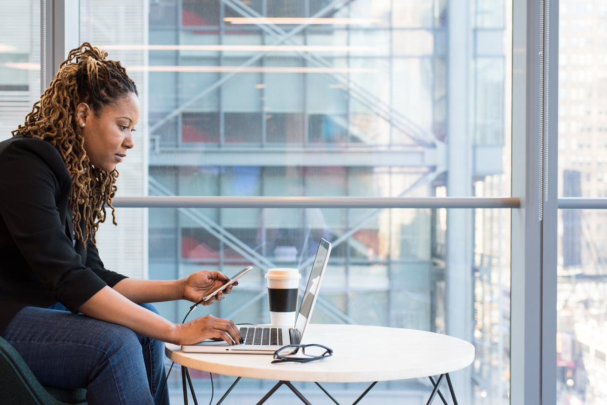 Woman working on a laptop near a large window