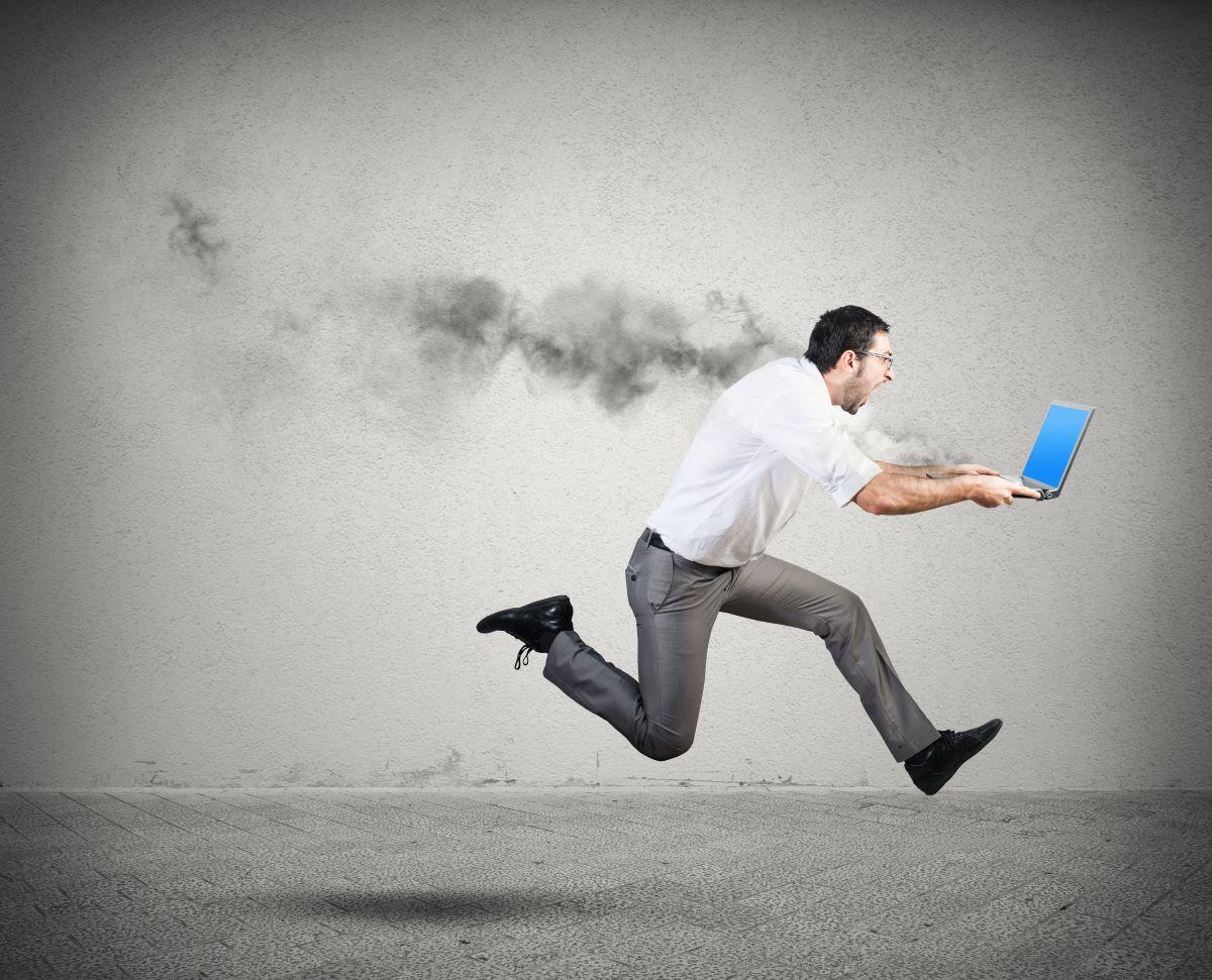 Ein schreiender Mann rennt mit einem rauchendem Laptop in seinen Händen.