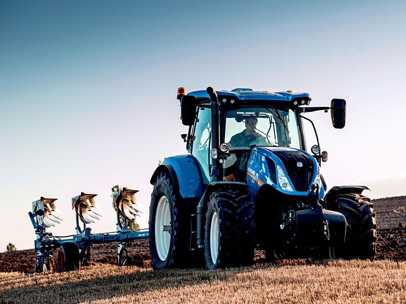Traktor med pløyer på åker