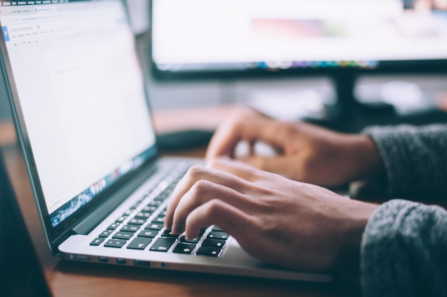 Hände schreiben auf einer Laptop Tastatur.