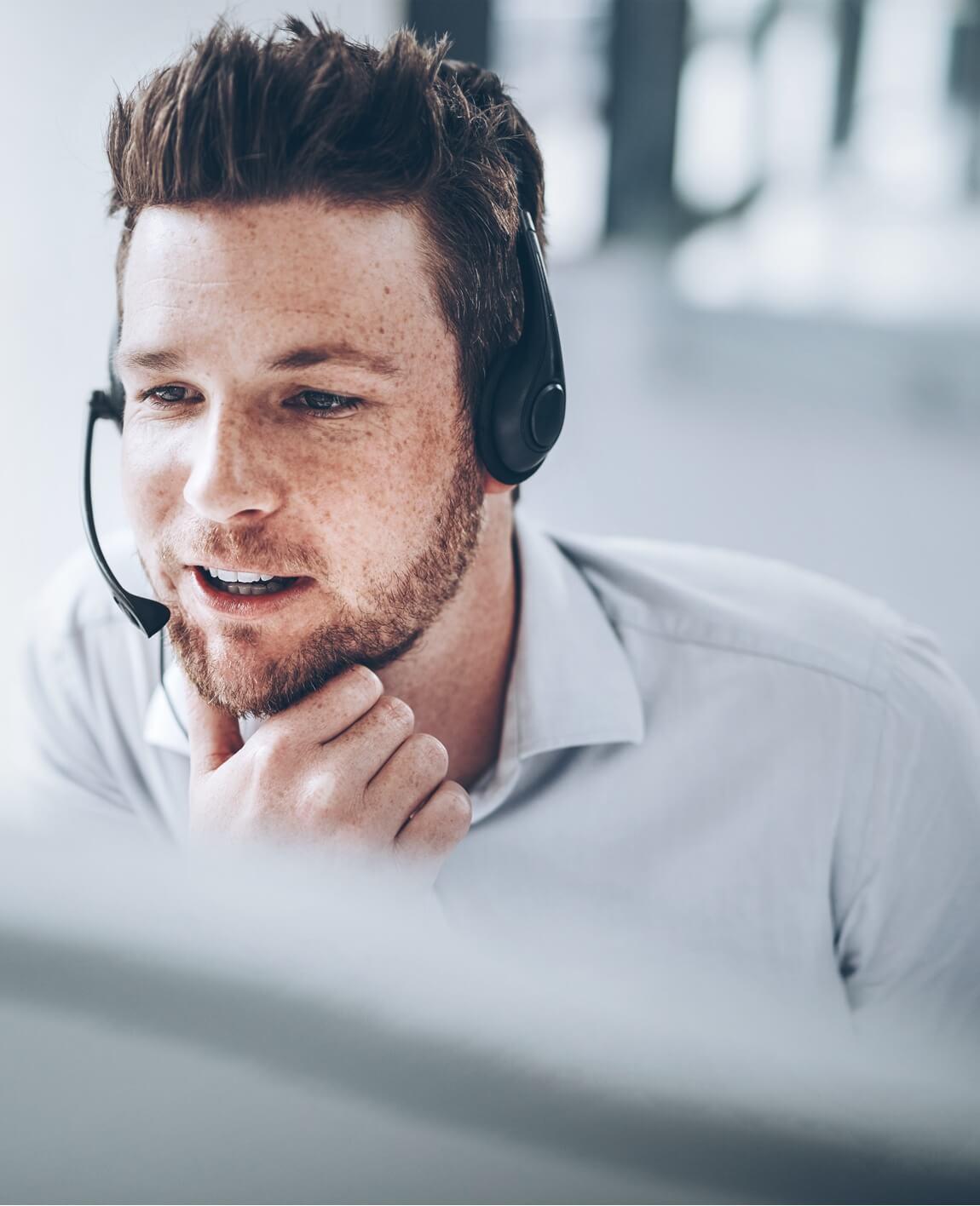 junger Mann mit Headset und Computer spricht mit Kunde zum Thema Datenschutz