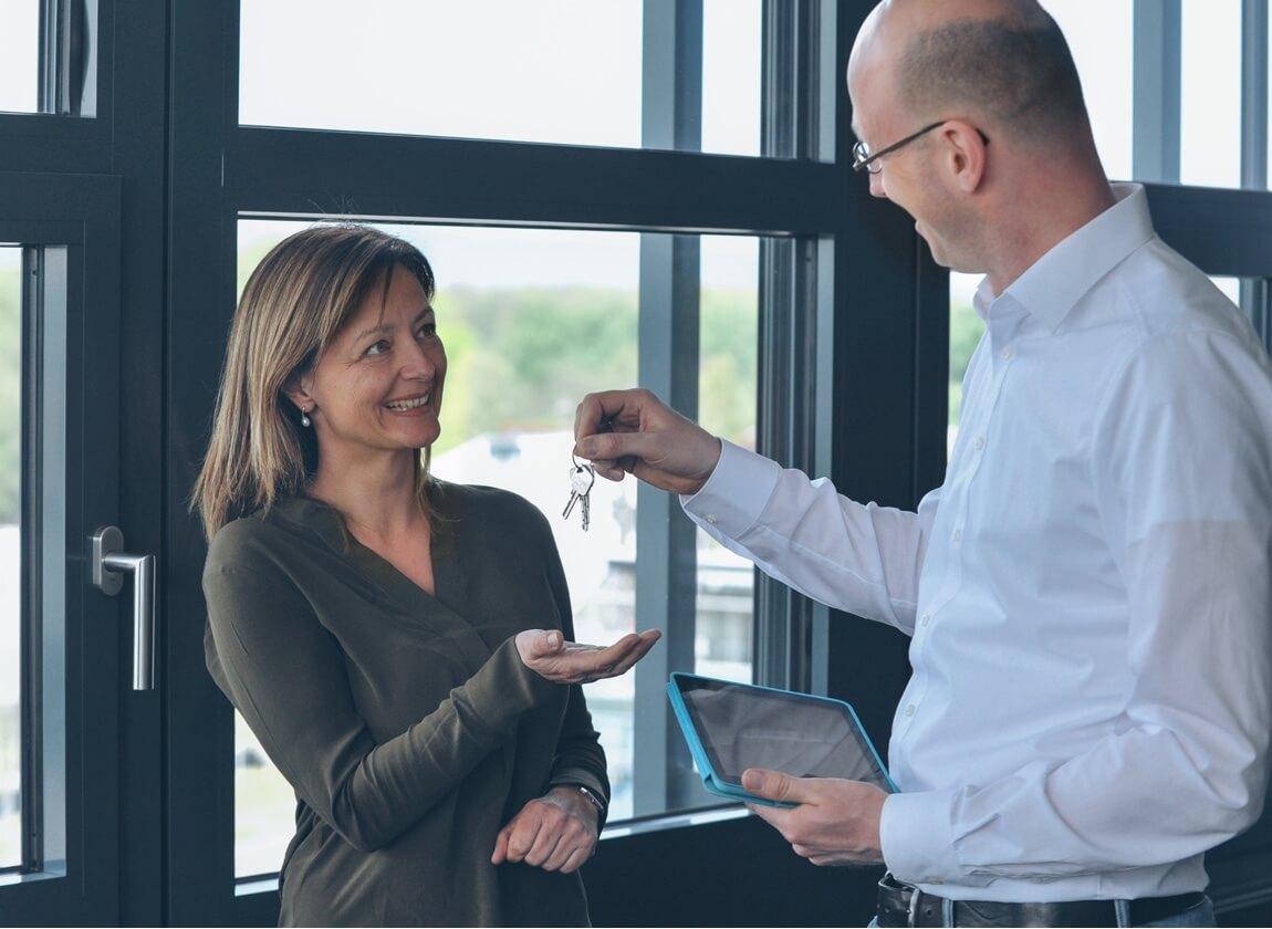 Mann mit Tablet übergibt einer Frau ihren Schlüssel