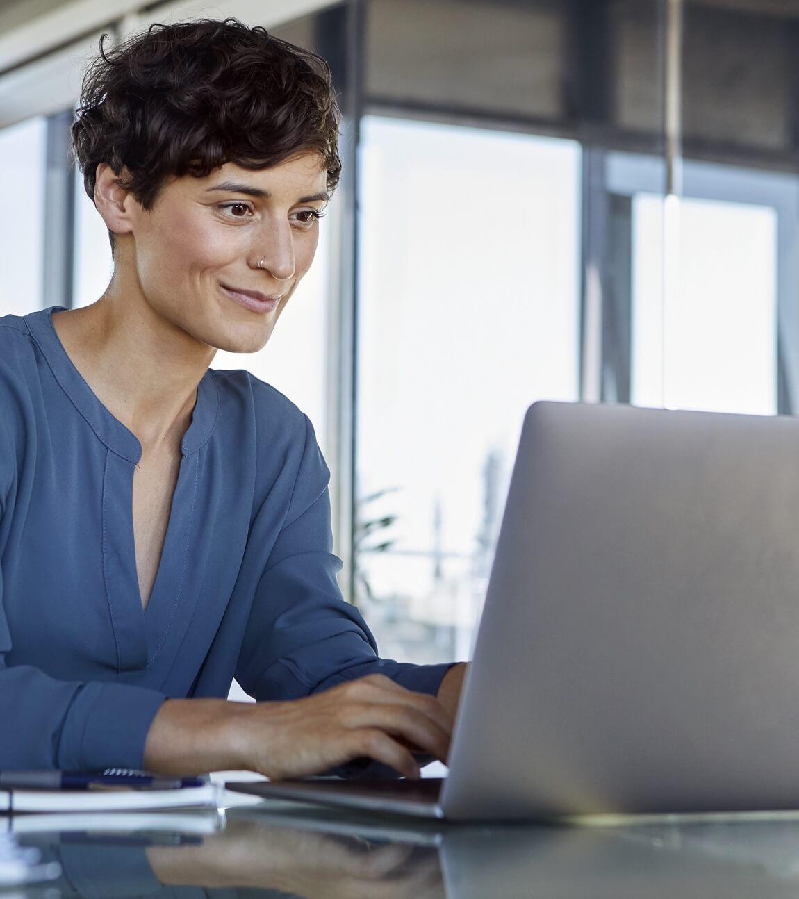 Frau arbeitet lächelnd am Rechner