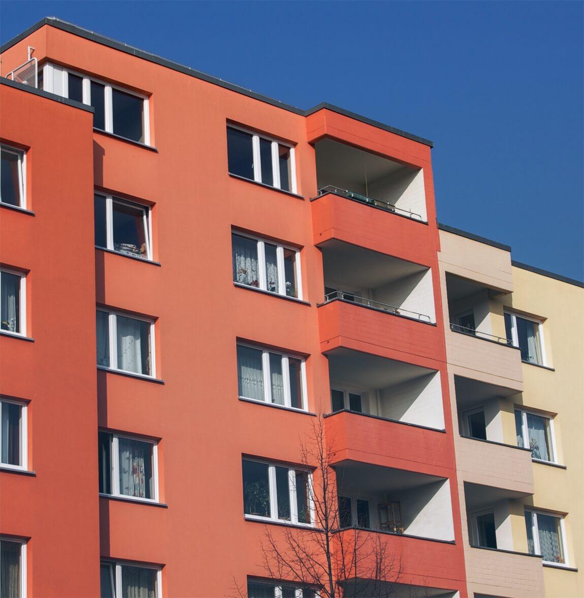 orange und gelbe Wohngebäude vor blauem Himmel