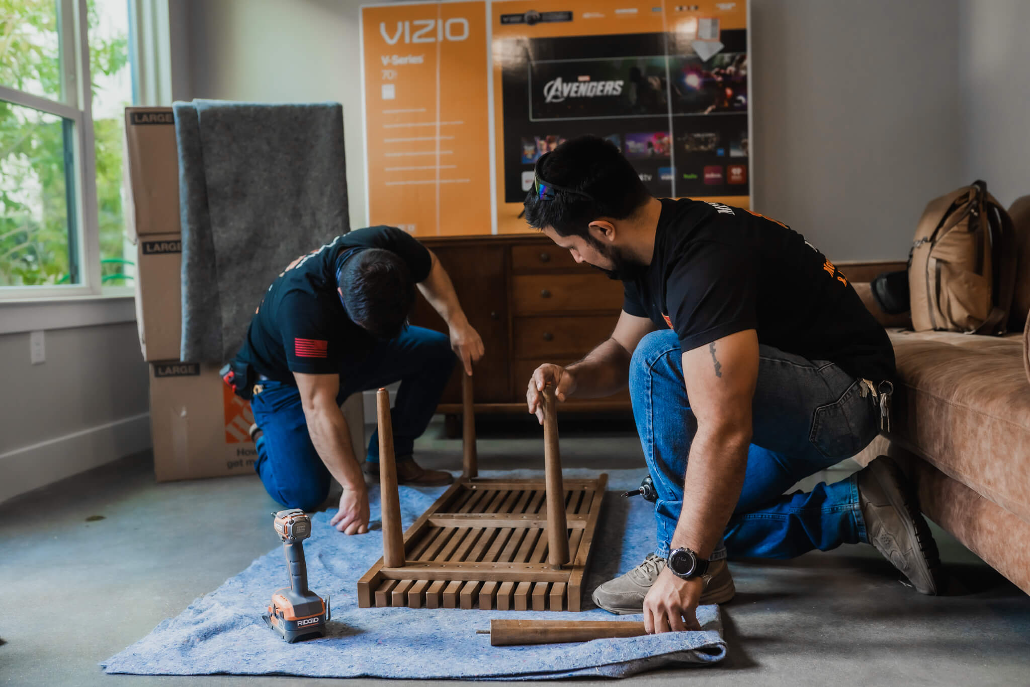Employees at Mission Minded helping one another assemble a table at a clients house.