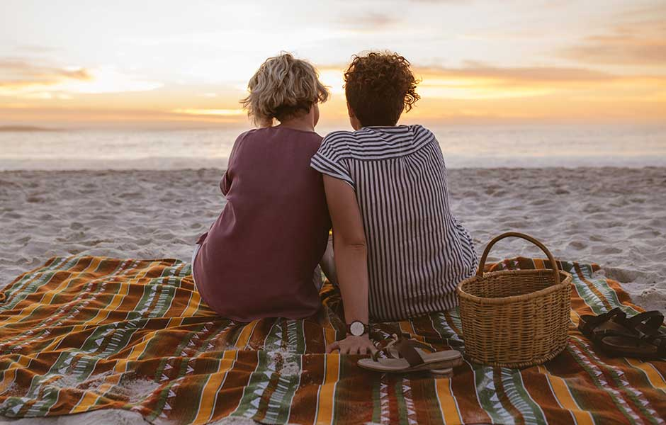 Kvinnligt par sitter på stranden och tittar på solnedgången