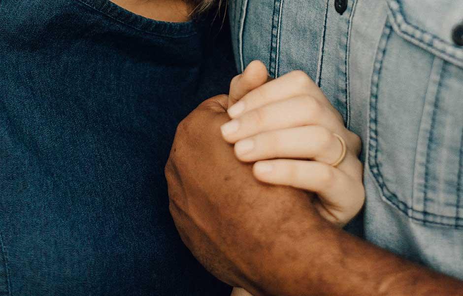 Närbild på kvinnas hand på mans arm