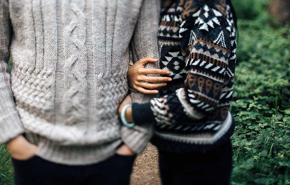 Par håller händer ute i skogen