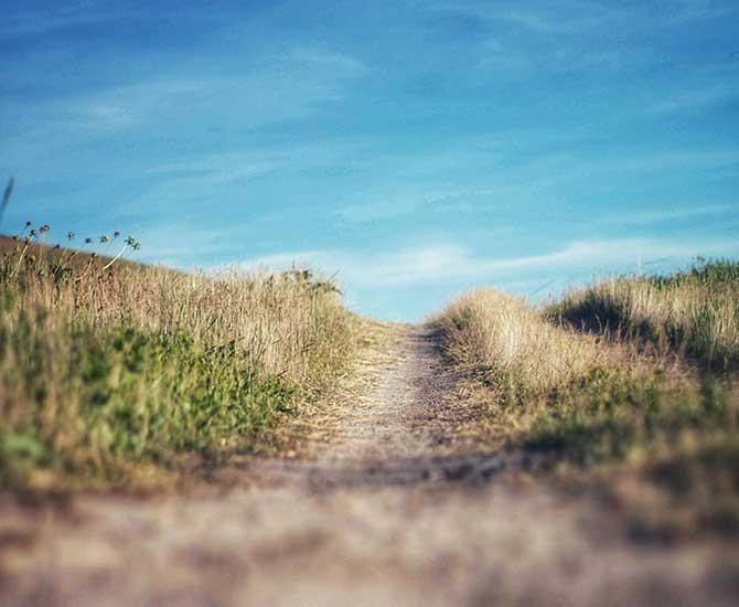 En stig genom landskap och blå himmel