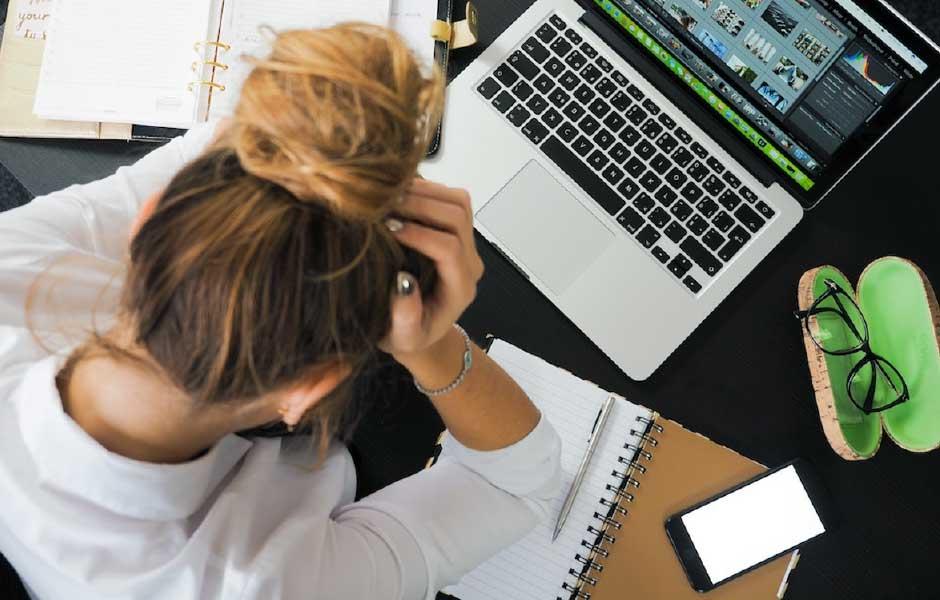 Stressad kvinna titta på laptop