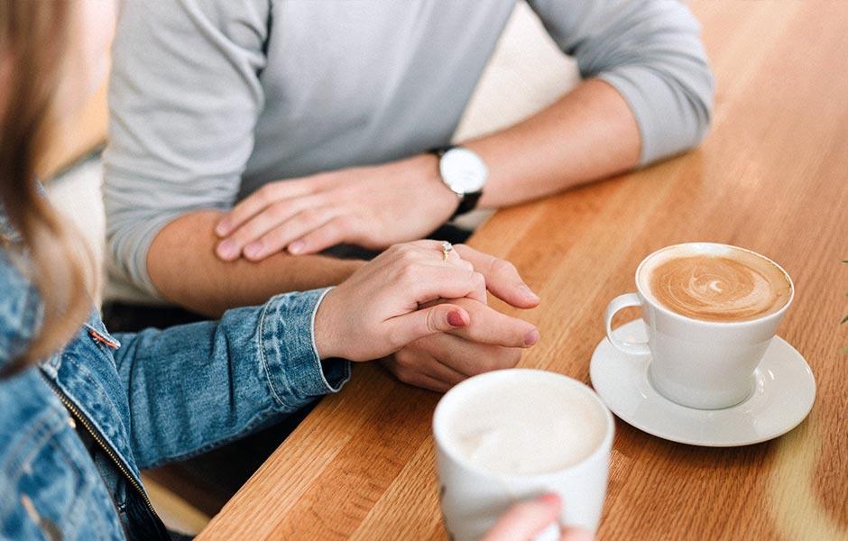 Par håller handen under en pratstund