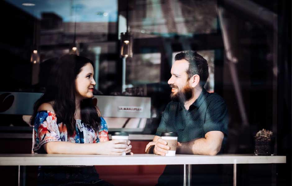 En man och en kvinna pratar över en kopp kaffe