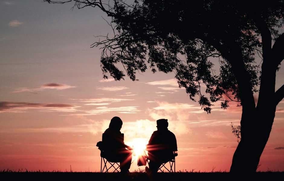 Ett par sitter vid ett träd och tittar på solnedgången