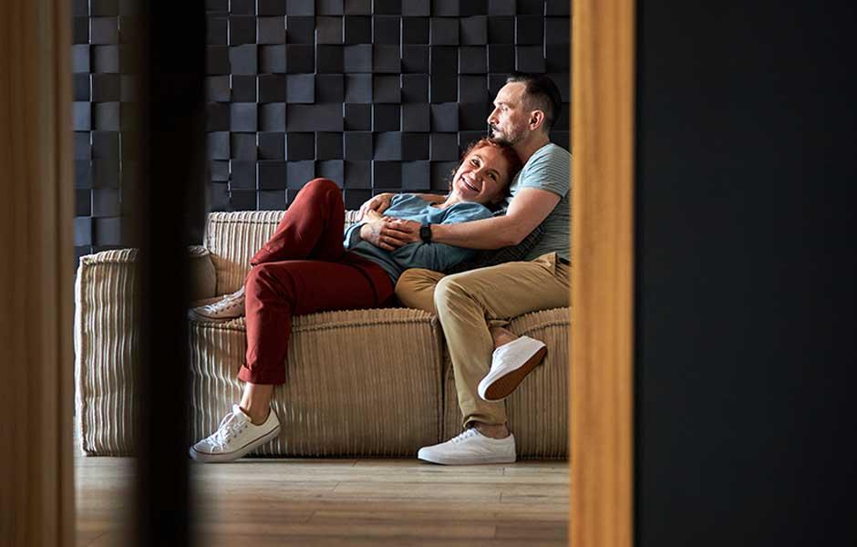 Par håller om varandra i en soffa