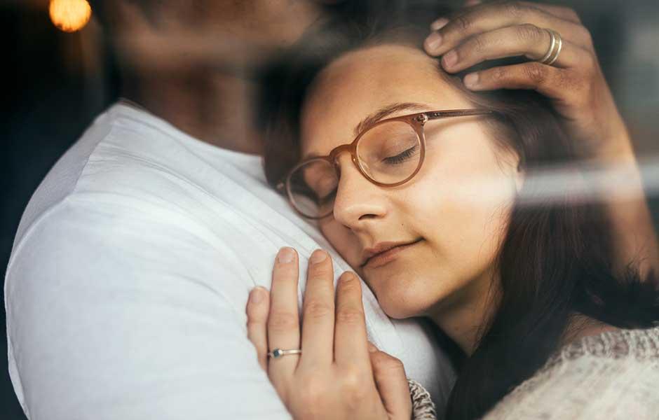 Kvinna är avslappnad i sin mans armar