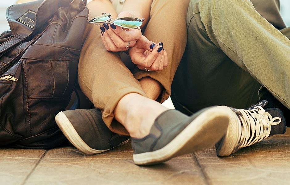 Ungt par sitter nära varandra på golvet