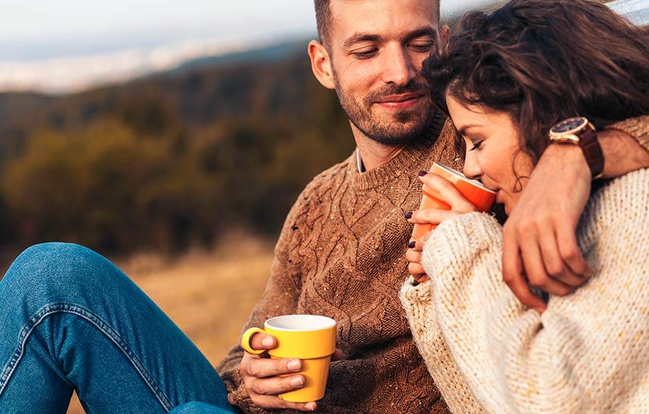 Par sitter nära varandra utomhus och dricker kaffe