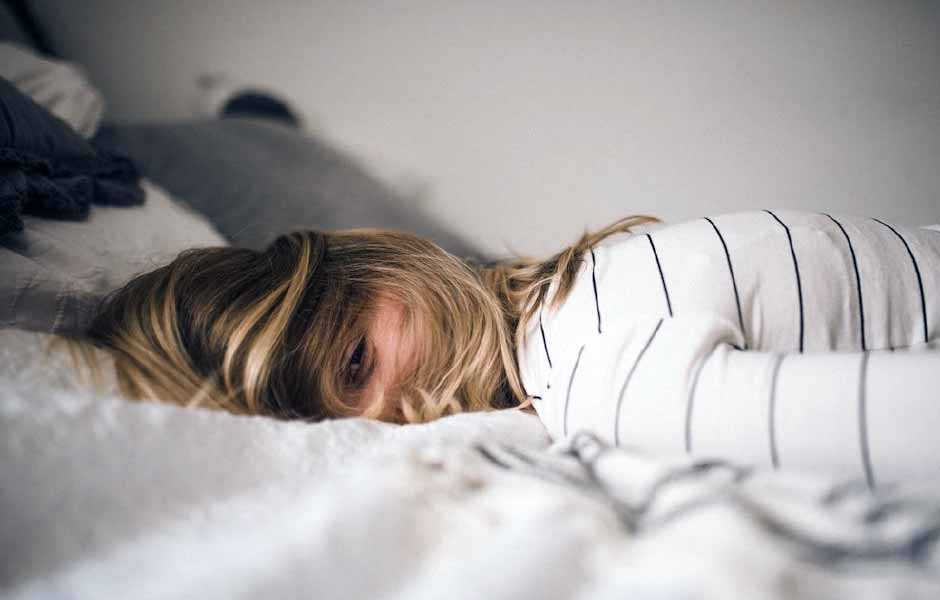 En kvinna ligger på sin säng och ser stressad ut