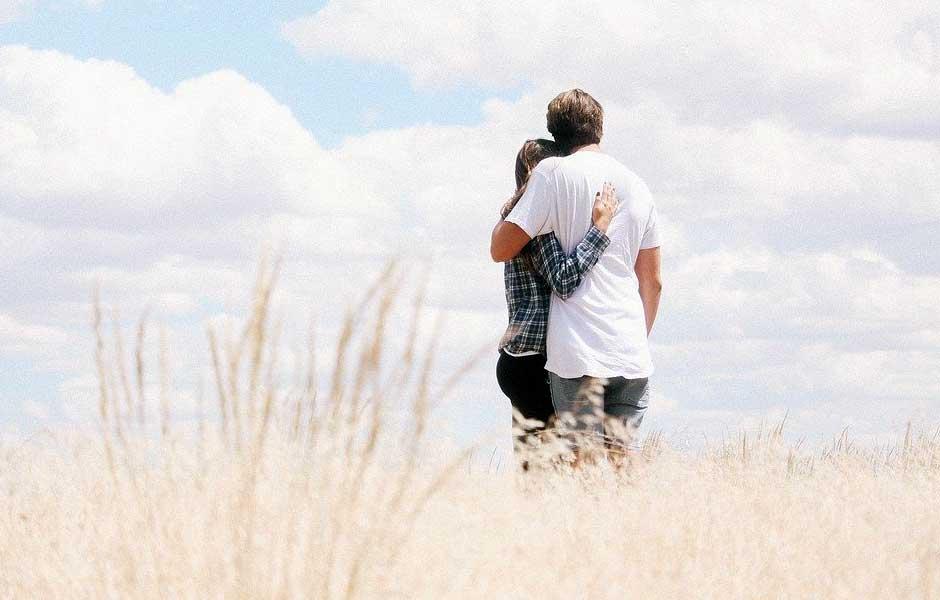 En man och en kvinna kramas i ett fält