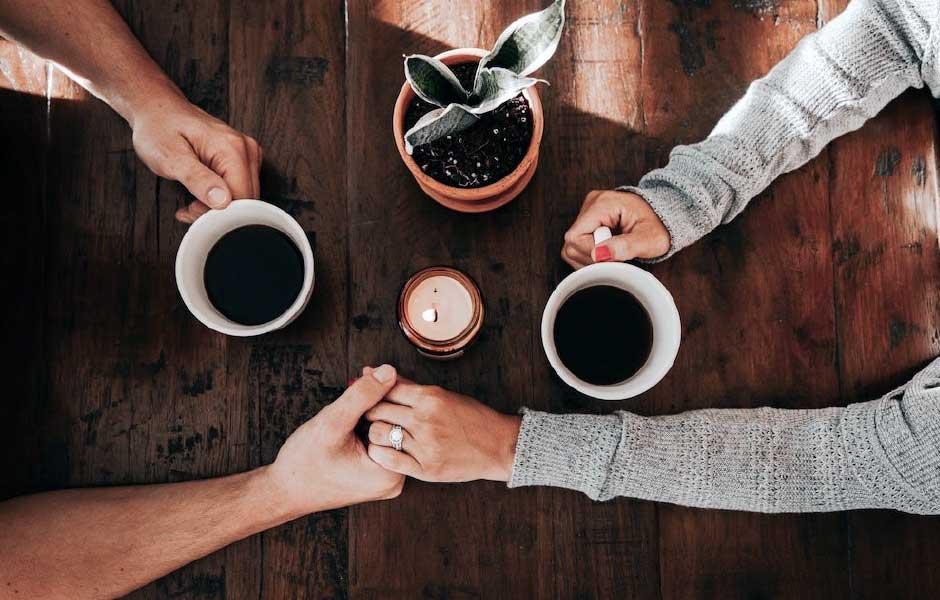 Ett par håller hand över ett träbord och dricker kaffe