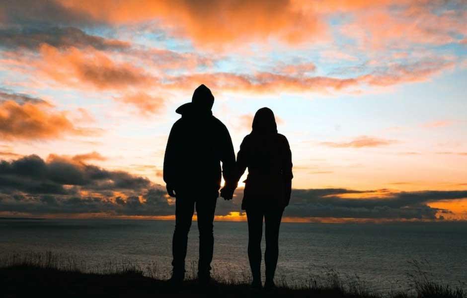 Ett par håller hand i solnedgången