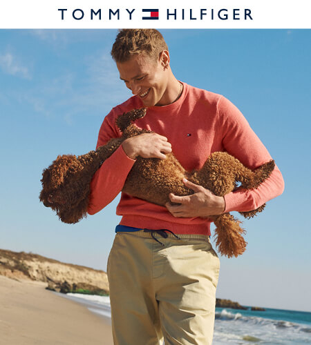 Young man wearing Tommy Hilfiger long-sleeve shirt and khaki pants holding his dog