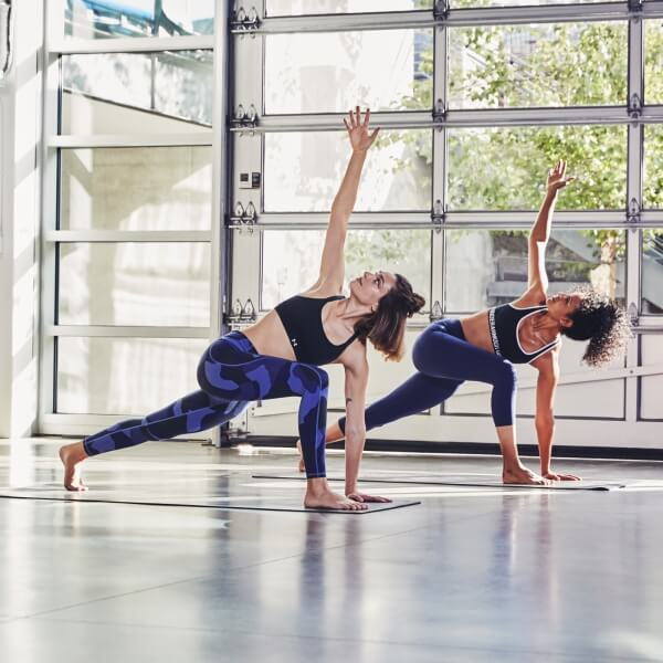 Two women doing yoga in Under Armour clothes