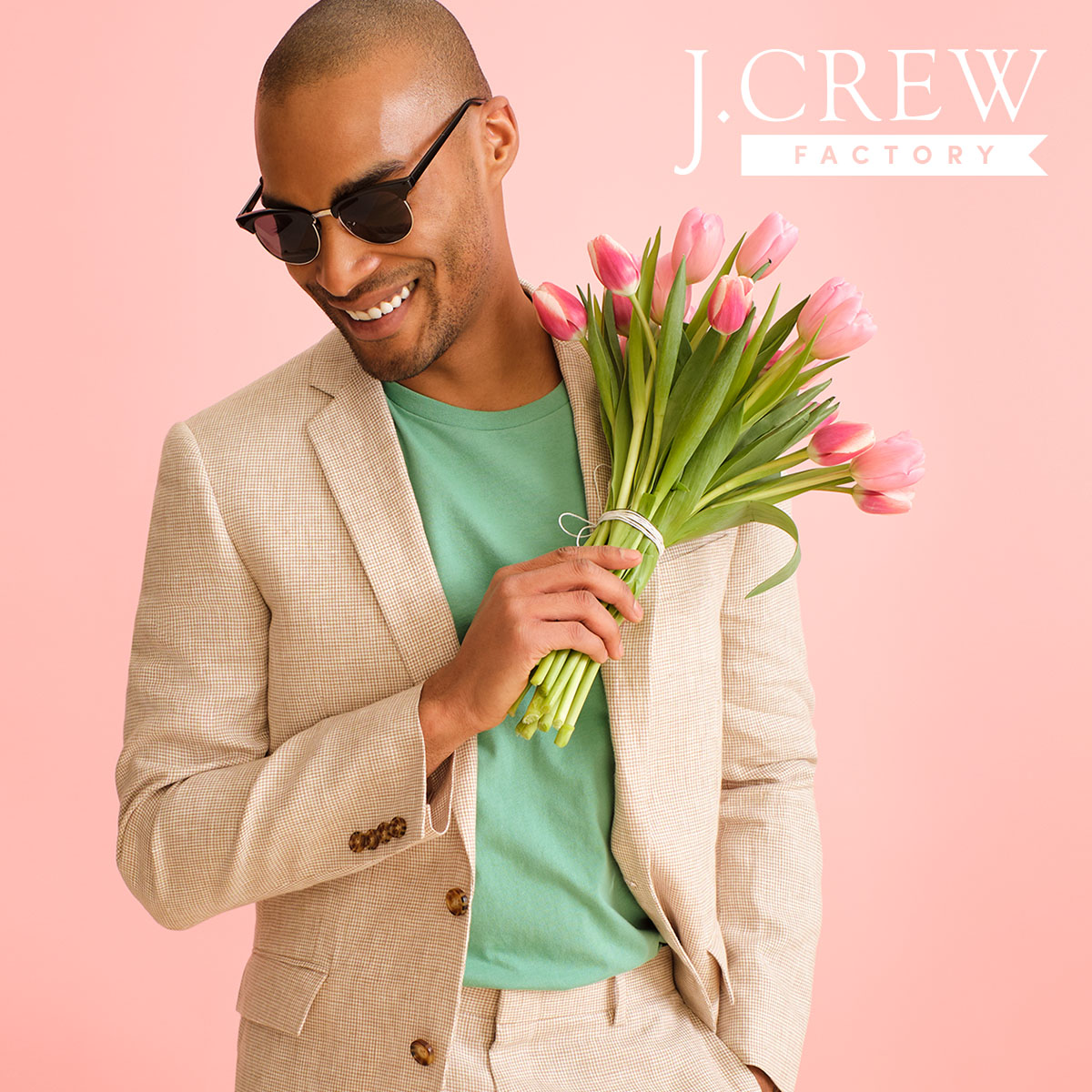 Man in a green shirt and tan coat holding tulips