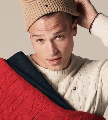 Young model wearing Tommy Hilfiger tan beanie and white sweater while holding matching red and navy sweaters.