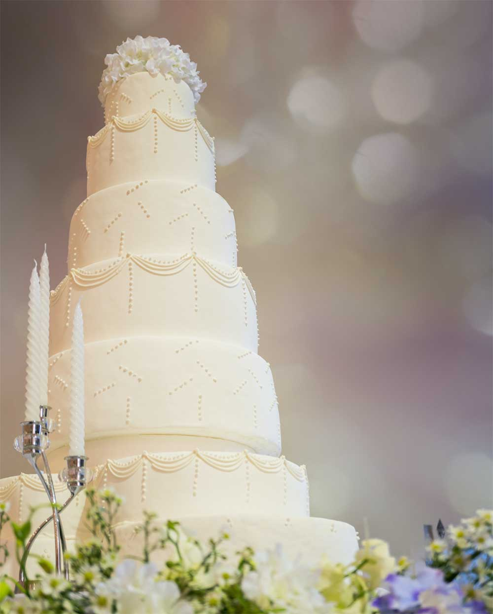 Four-tier wedding cake surrounded by flowers and candles, weddings in Huntsville