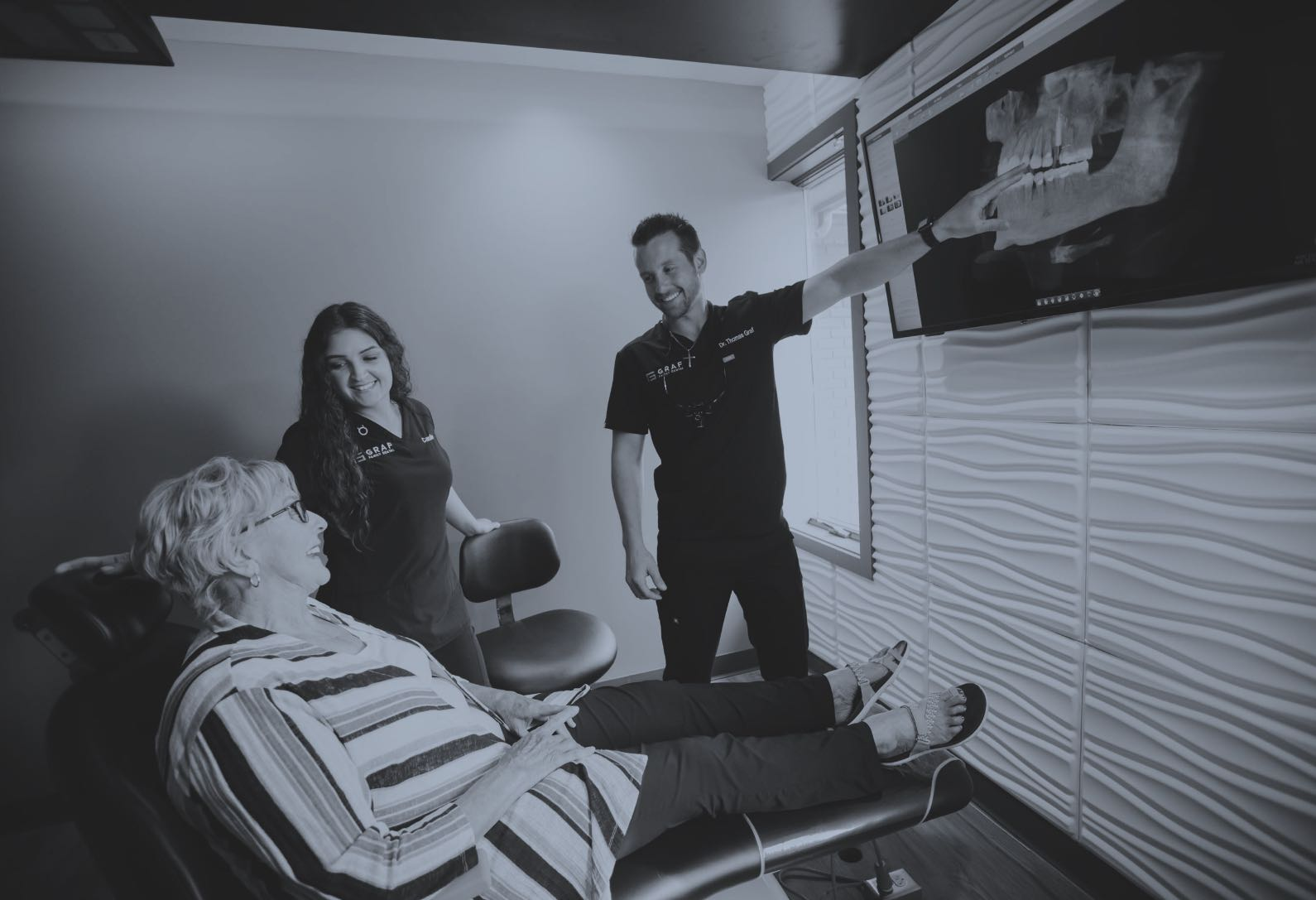 Photo of a patient, team member, and Dr. Graf pointing at an x-ray image on a screen