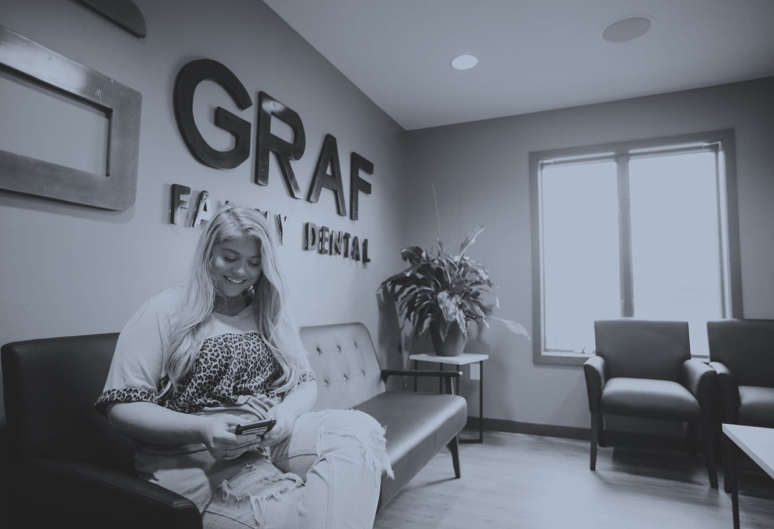 Photo of a patient sitting in the lobby looking at her phone