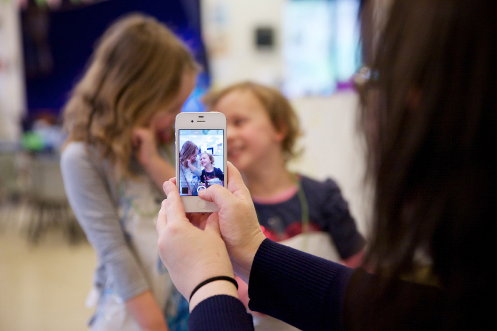 Teacher taking photo of toddlers with a smartphone