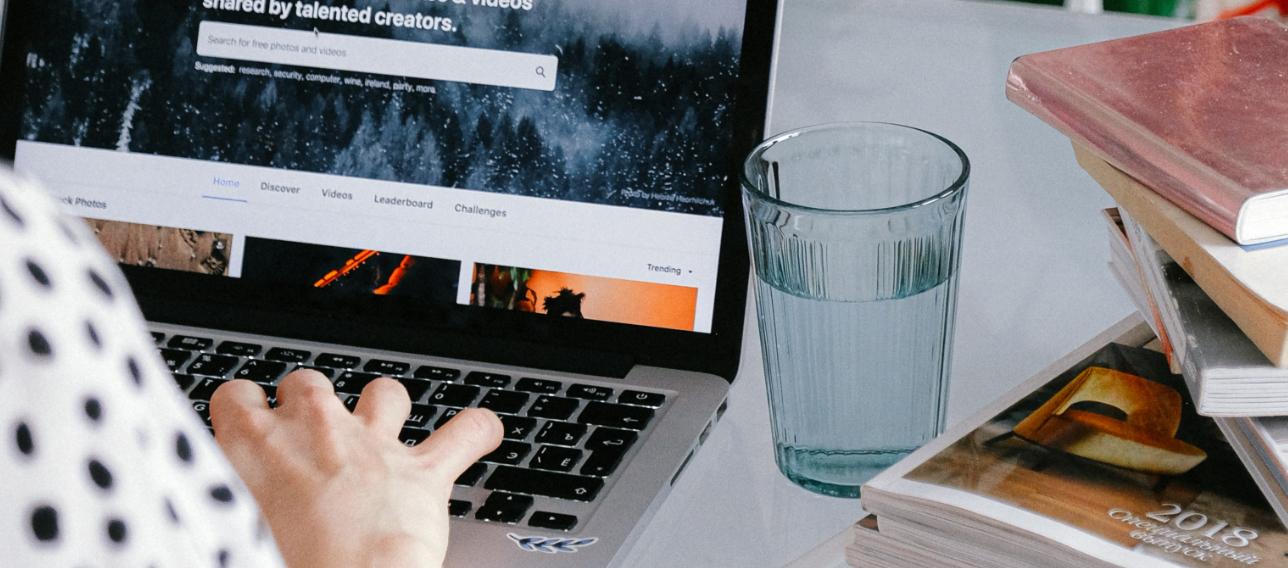 Bord med laptop, glass vann og bøker