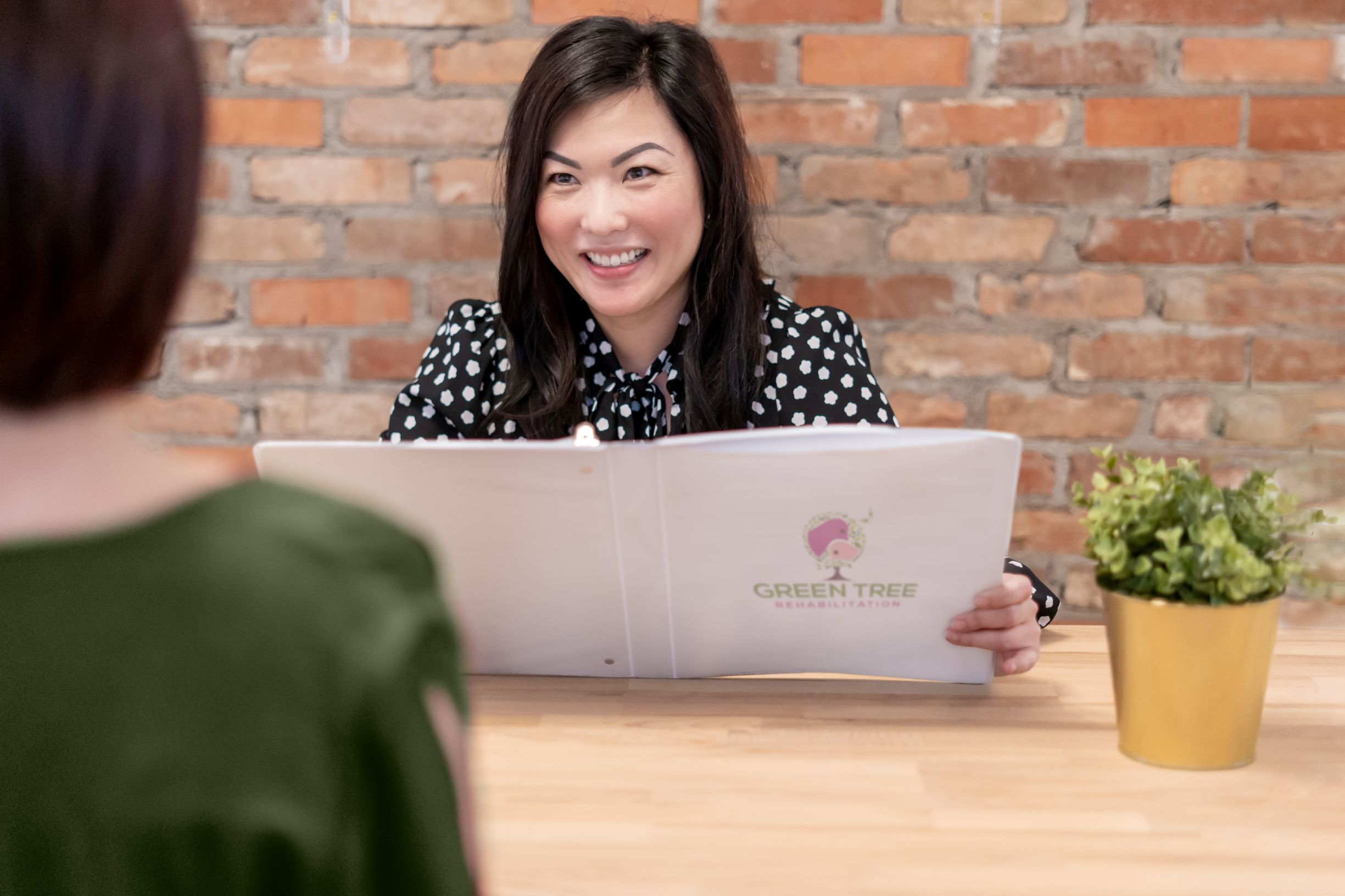 Occupational therapist smiling, and welcoming client while sitting across the desk from them.