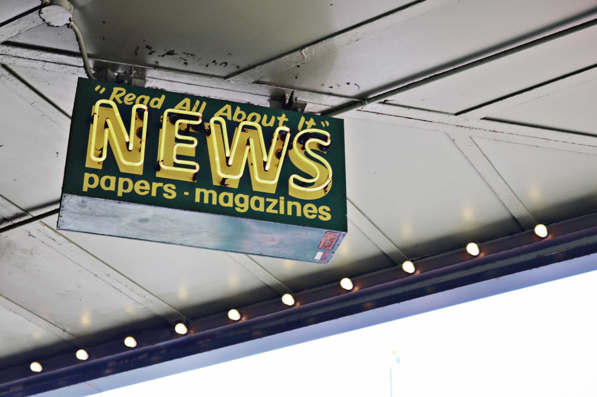 a news stand sign in yellow and green that reads read all about it news paper magazine