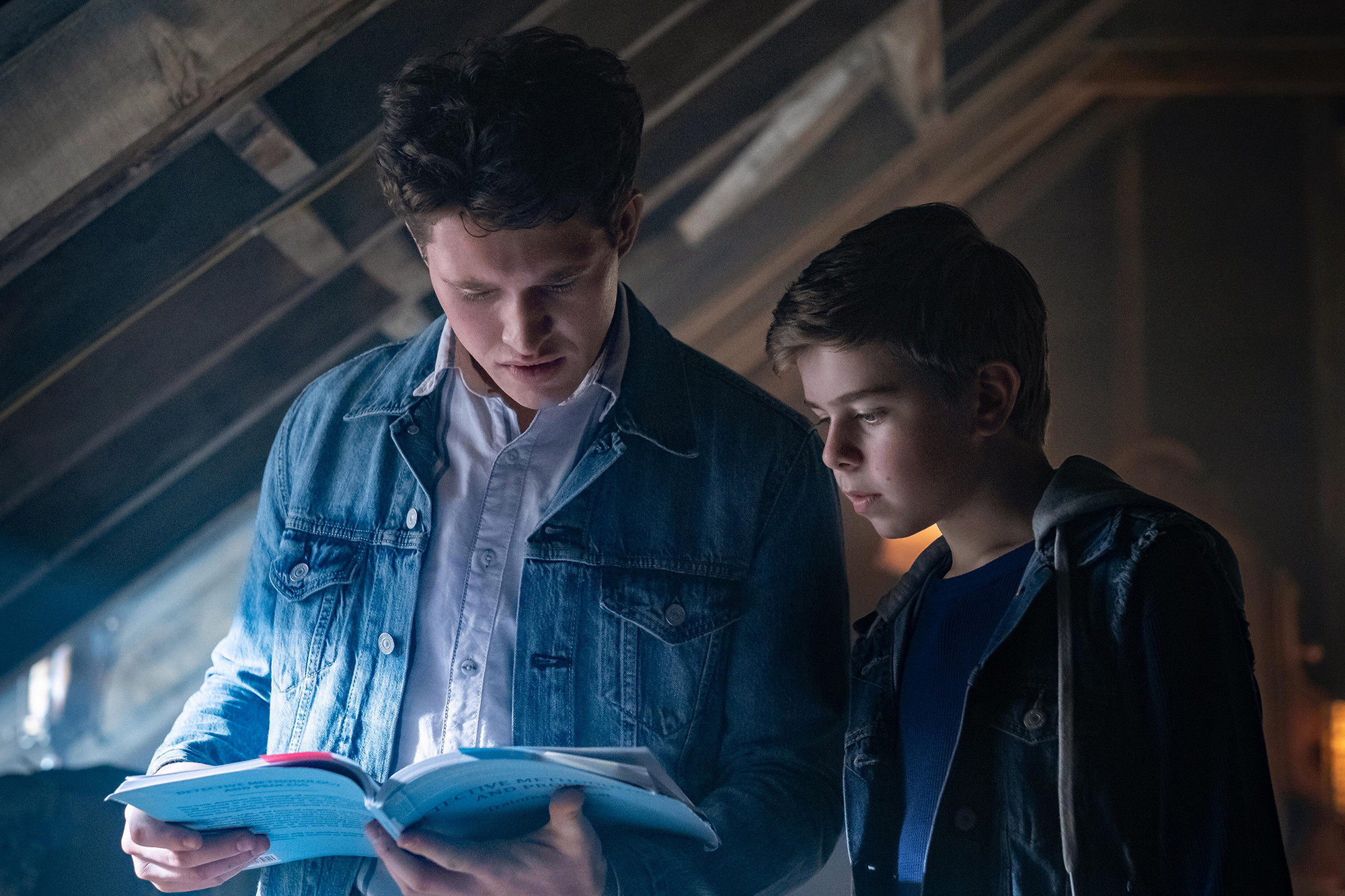 2 teenagers reading a paper in a dark attic