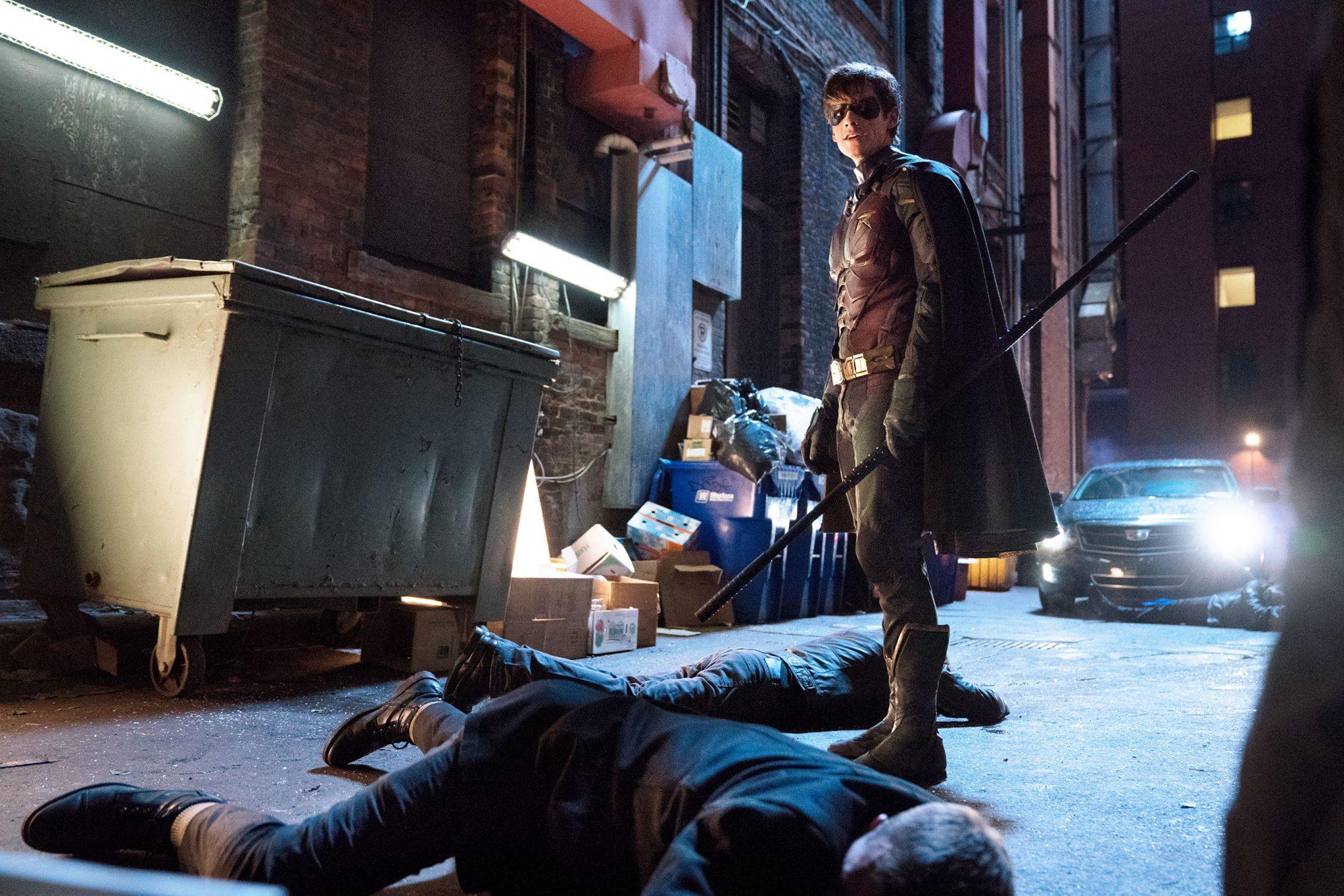 Superhero saving someone on the floor in dark back alley
