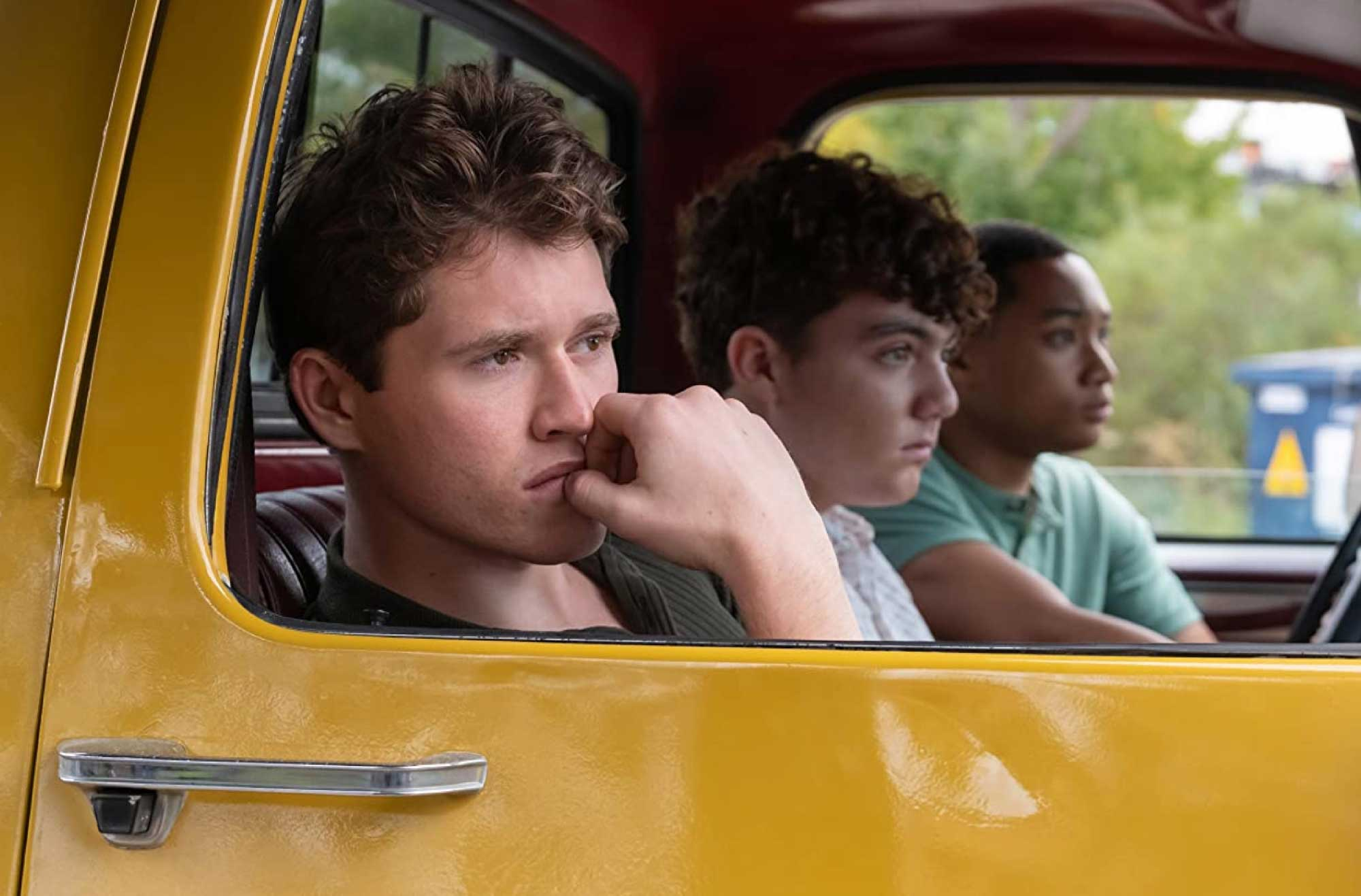 3 boys in a vintage yellow car
