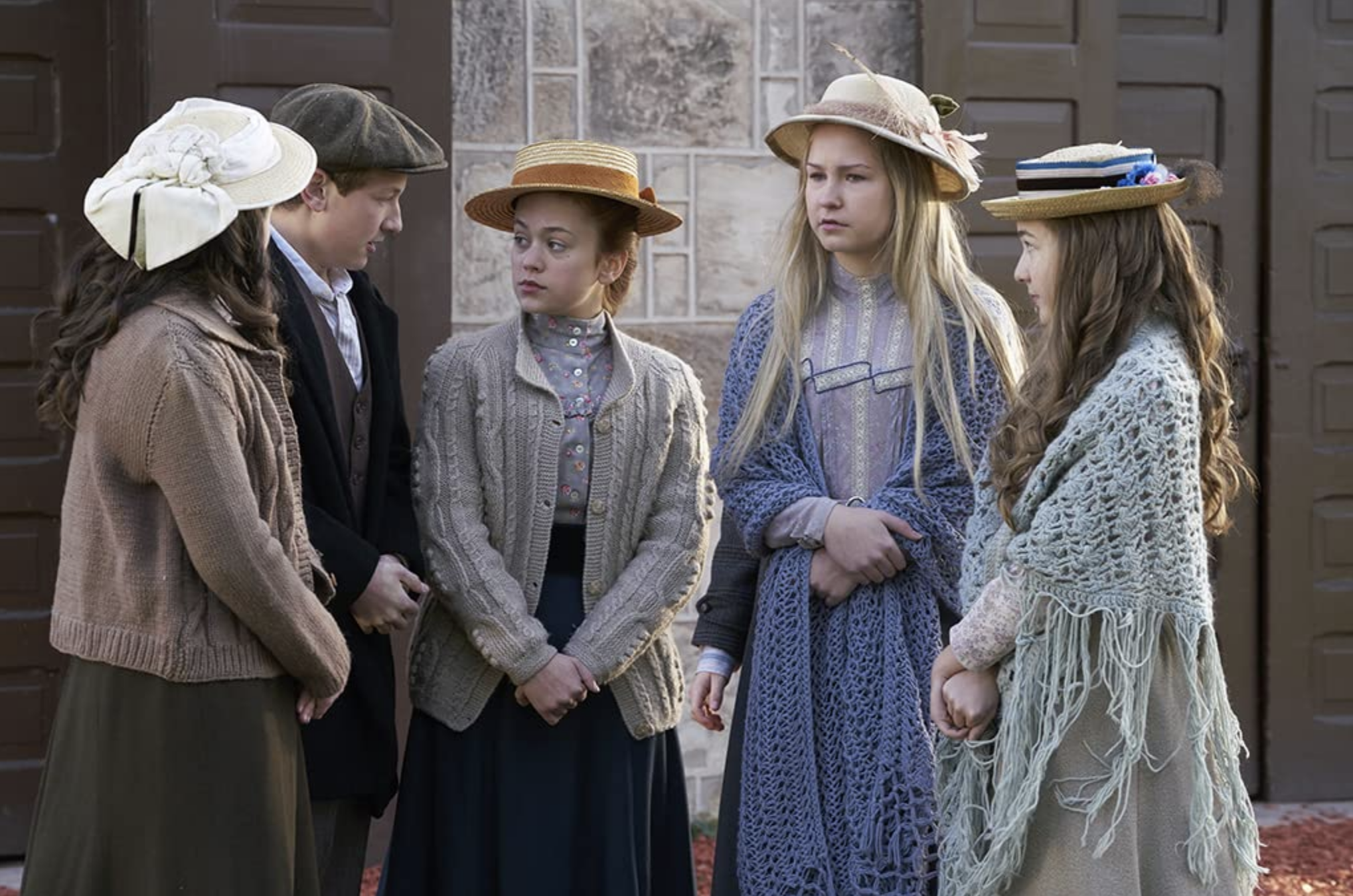 4 preteens in turn of the century clothes outside church school